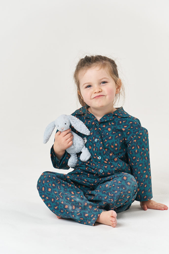 Jasmine sat cross-legged in her Pomegranate Pyjamas, holding a bunny soft toy and smiling