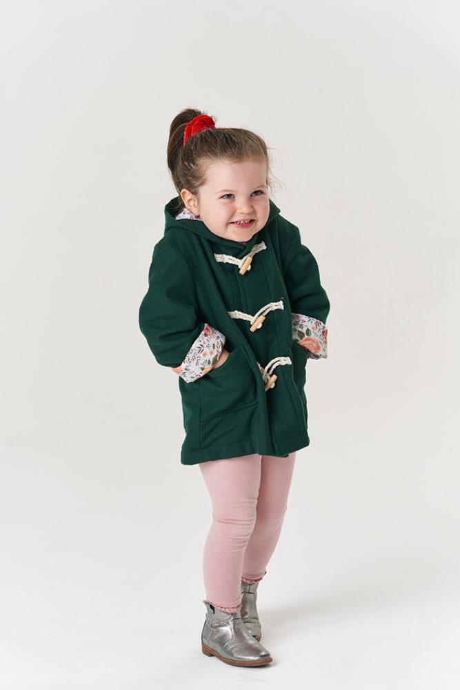 Jasmine wearing the Poppy & Jazz Walnut Duffle Coat, scrunching up her shoulders with her hands in her pockets