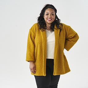 Chantelle modelling the Jessie Coatigan in a gorgeous mustard yellow boucle and stood with one hand on her hip