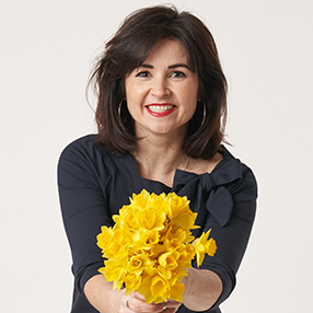 Lisa wearing the Audrey Top while holding a bunch of bright yellow flowers and smiling